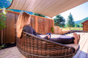 Doc-Holidays-Cabin-Deck-–-with-woman-sitting-in-outdoor-lounge-drinking-coffee-300x200.jpg